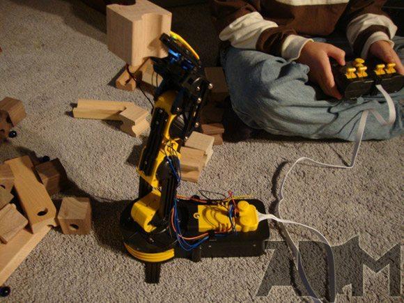 Robot Arm holding a wooden block on carpet